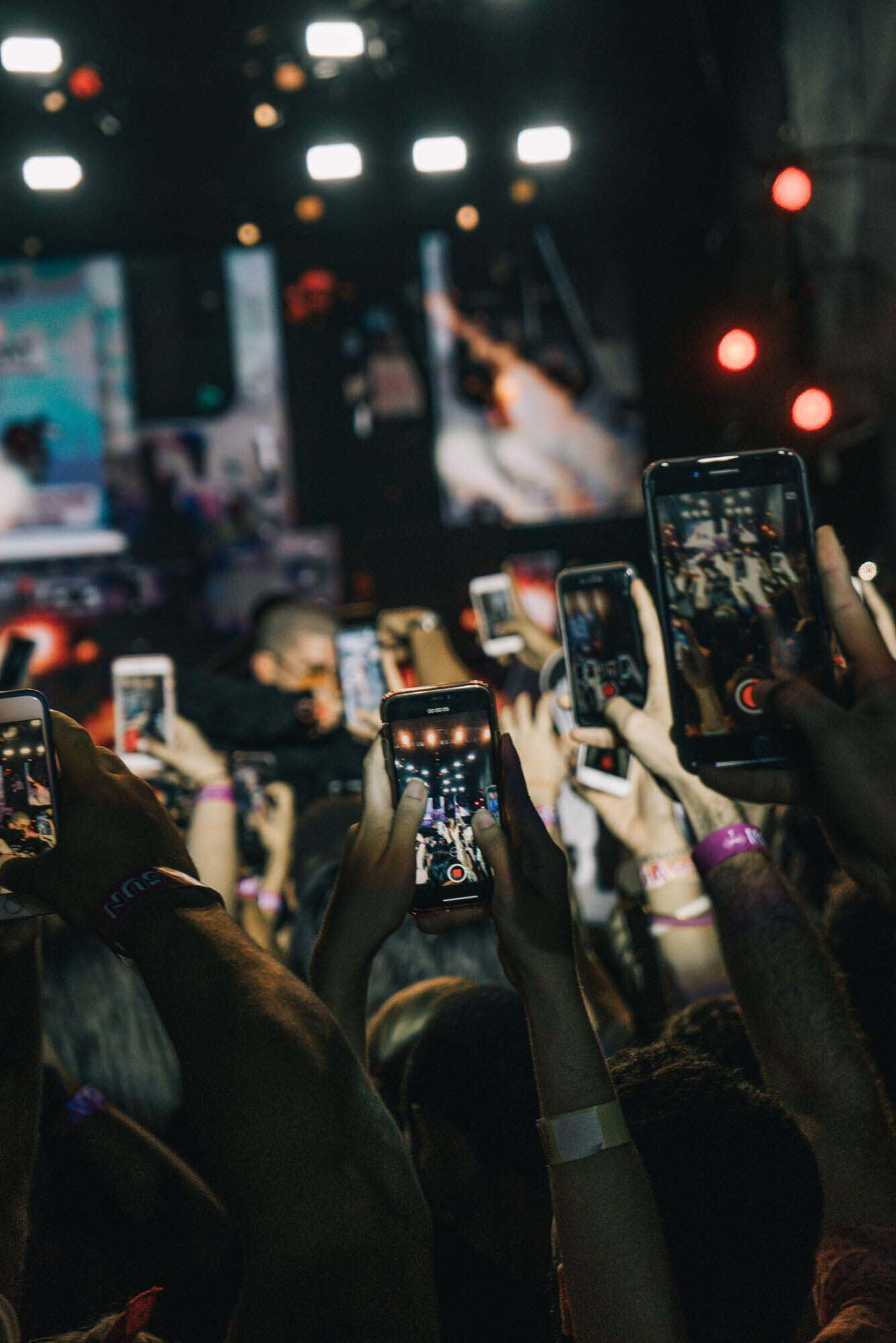 Dozens of hands hold phones up to record a concert performance